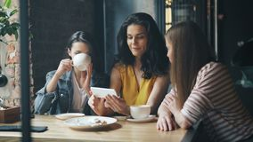 Grupp av unga kvinnor som håller ögonen på smartphoneskärmen som skrattar dricka kaffe i kafé lager videofilmer