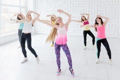 Grupp av unga kvinnor som poserar med lyftta armar, medan ha en konditiondansgrupp fotografering för bildbyråer