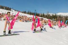 Grupp av unga lyckliga nätta kvinnor på en snowboard i färgrik bikini med flaggor Arkivbilder