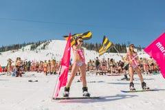 Grupp av unga lyckliga nätta kvinnor på en snowboard i färgrik bikini med flaggor Fotografering för Bildbyråer