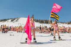Grupp av unga lyckliga nätta kvinnor på en snowboard i färgrik bikini med flaggor Royaltyfria Bilder