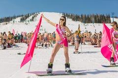 Grupp av unga lyckliga nätta kvinnor på en snowboard i färgrik bikini med flaggor Royaltyfria Foton