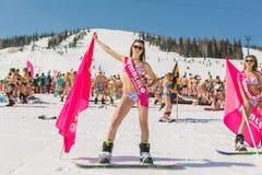 Grupp av unga lyckliga nätta kvinnor på en snowboard i färgrik bikini med flaggor Royaltyfri Bild