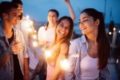 Grupp av unga lyckliga v?nner som har partiet och gyckel royaltyfri bild