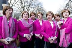 Grupp av unga män som poserar som Angela Merkel Arkivbilder