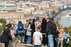 Grupp av unga och gamla turister som står på en synvinkel upp höjdpunkt för att ta bilder av staden Budapest Arkivbilder