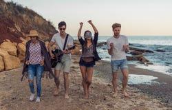 Grupp av unga och gladlynta vänner som går på stranden arkivbilder
