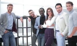 Grupp av unga professionell som står i kontoret fotografering för bildbyråer