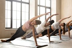 Grupp av unga sportiga kvinnor som öva yoga som gör Vasisthasana royaltyfri bild
