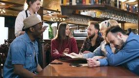 Grupp av unga stiliga vänner som gör beställning från meny till den le servitrins i stången, bar arkivfilmer