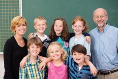 Grupp av unga studenter som poserar med deras lärare royaltyfri bild