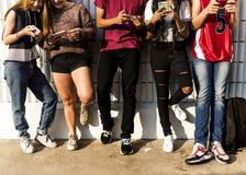Grupp av unga tonåringvänner som kyler ut tillsammans genom att använda socialt massmediabegrepp för smartphone royaltyfria bilder