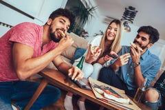 Grupp av unga vänner som äter pizza och håller ögonen på tv Registreringsapparat och korpsvart arkivbild