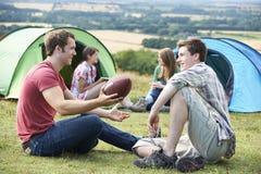Grupp av unga vänner som campar i bygd Royaltyfri Bild