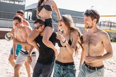 Grupp av unga vänner som går på strandvolleybolldomstolen royaltyfria bilder
