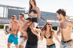 Grupp av unga vänner som går på strandvolleybolldomstolen royaltyfria foton