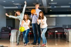 Grupp av unga vänner som spelar bowling Royaltyfri Bild