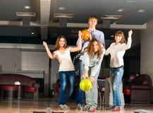 Grupp av unga vänner som spelar bowling Arkivfoton