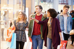 Grupp av unga vänner som tillsammans shoppar i galleria royaltyfri bild