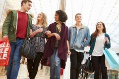 Grupp av unga vänner som tillsammans shoppar i galleria Royaltyfria Foton