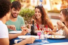 Grupp av unga vänner som tycker om mål i utomhus- restaurang Royaltyfri Bild