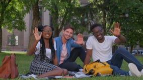 Grupp av unga vänner som vinkar deras armar som gesthälsningbegrepp l?ngsam r?relse lager videofilmer