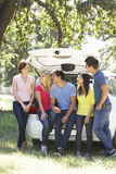Grupp av unga vänner som sitter i stam av bilen Arkivbilder