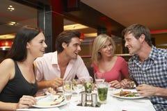 Grupp av unga vänner som tycker om mål i restaurang Arkivbilder