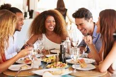 Grupp av unga vänner som tycker om mål i utomhus- restaurang Arkivfoton