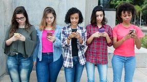 Grupp av unga vuxna kvinnor som spelar med telefonen Royaltyfria Foton
