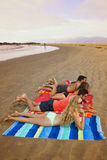 Grupp av unga vuxna människor på stranden Arkivbild
