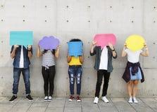 Grupp av unga vuxna människor som rymmer utomhus det tomma plakatet royaltyfri fotografi