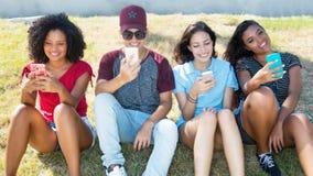 Grupp av unga vuxna människor som surfar det netto med telefoner royaltyfria foton
