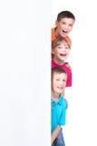 Grupp av ungar bak det vita banret Royaltyfri Foto