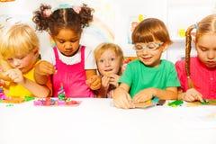Grupp av ungar i dagislek med plasticine royaltyfri fotografi