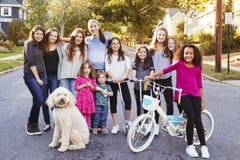 Grupp av ungar med hundleende till kameran i en bostads- gata royaltyfria foton