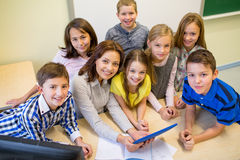 Grupp av ungar med lärare- och minnestavlaPC på skolan arkivbilder