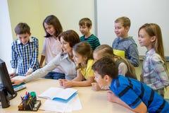 Grupp av ungar med läraren och datoren på skolan Royaltyfria Bilder