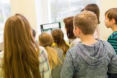 Grupp av ungar med läraren och datoren på skolan arkivbild