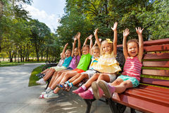 Grupp av ungar på bänkbifalllyftande händerna Arkivbilder