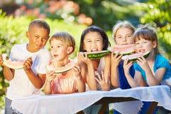 Grupp av ungar som äter melon Royaltyfri Bild