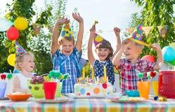 Grupp av ungar som har gyckel på födelsedagpartiet Arkivfoto