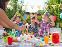 Grupp av ungar som har gyckel på födelsedagpartiet Royaltyfri Fotografi