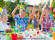 Grupp av ungar som har gyckel på födelsedagpartiet Royaltyfria Bilder