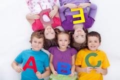 Grupp av ungar som rymmer alfabetiska bokstäver Royaltyfria Foton