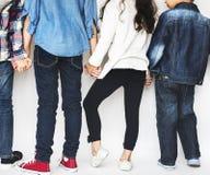 Grupp av ungar som rymmer händer bak bakre sikt på vit bakgrund Royaltyfri Bild