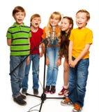 Grupp av ungar som sjunger till mikrofonen Arkivfoto