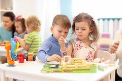 Grupp av ungar som spelar i dagis Barn som bygger leksakhuset med plast- kvarter som tillsammans sitter vid tabellen royaltyfria foton