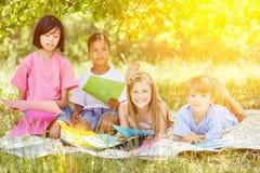 Grupp av ungar som spelar och grejar i trädgården Royaltyfri Fotografi