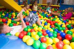 Grupp av ungar som spelar på lekplats med plast- bollar Royaltyfria Bilder